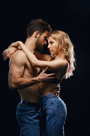 man kissing passionate fair-haired woman isolated on black background. studio shot. Banque d'images