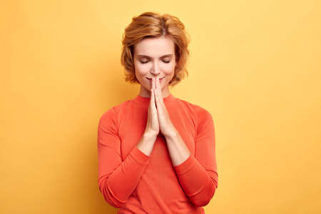 Young smiling girl with closed eyes keeps palms together, makes request, prays, pleads for mercy, asking help, health. Isolated over yellow background.close up portrait , woman makes a wish Archivio Fotografico