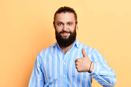 Happy man in stylish shirt showing thumb up, expressing positive emotion, isolated yellow background. studio shot. gesture concept