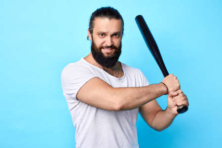 strong muscular young man holding baseball bat and going to kick , hit the ball isolated on blue, isolated blue background. hobby, free time, spare time, lifestyle