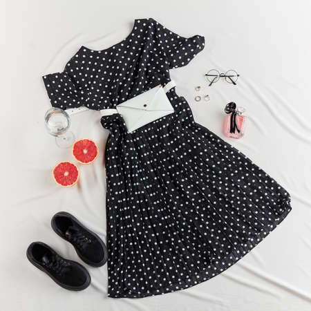 Summer womens clothing and accessories: black dress, trainers, glasses, rings, perfume, wallet, bag Summer fashion shopping concept