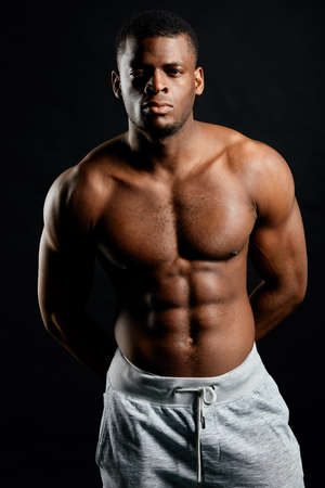 muscular serious bodybuilder with hands on his back looking at the camera. body and health care, beauty.isolated black background. close up portrait.