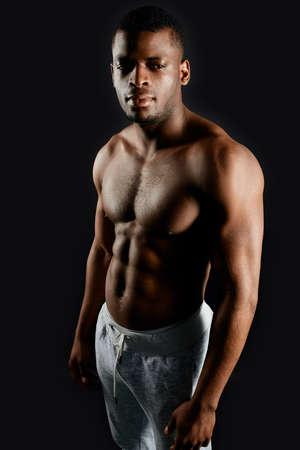 Agradable chico africano guapo con hermoso cuerpo de pie sobre fondo negro apariencia, concepto de personas