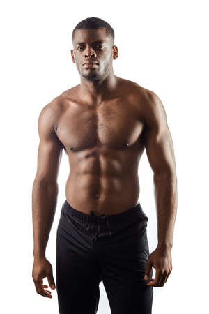 cool shirtless slim Afro American man in trousers looking at the camera.isolated white background, beauty, wellness, wellbeing.