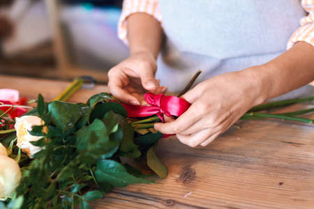 close up cropped photo of female florist making bunch and tying ribbon at flower shop. Imagens