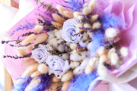 Wedding bouquet of white, blue roses lying on wooden floor. close up portrait, creative fowers for lover. business, sale, discount