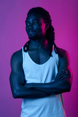muscular strong afro sportsman having a break during training, close up portrait, isolated violet background, studio shot Archivio Fotografico
