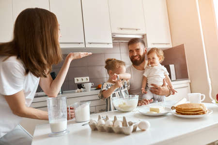 funny crazy brown-haired mommy blowing flour to his husband and kids, entertainment. close up photo Imagens