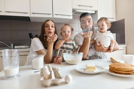 funny family having fun in the kitchen, parents and kids blowing flour, close up photo. entertainment concept Imagens