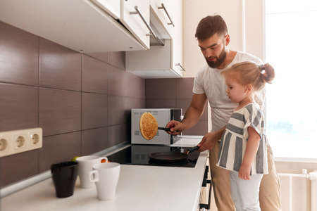 handsome dad and his adorable daughter preparing pancakes in the kitchen.lifestyle, free time, spare time . copy space