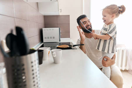 plesant positive dad and his kid having fun in the kitchen while cooking pancakes for breakfast. close up side view photo. copy space