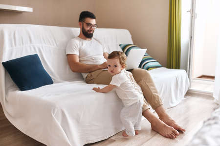 smiling young father enjoying working on laptop, while his baby leaning on the sofa and looking at the camera. close up photo Stock Photo