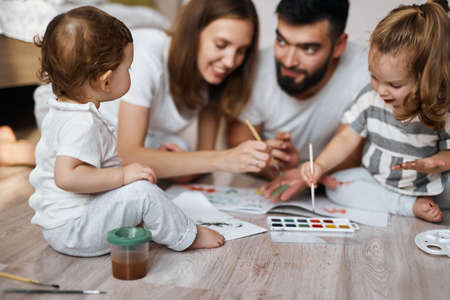 nice little baby looking at her parents and elder sister who are spending time on painting. blurred background Banco de Imagens
