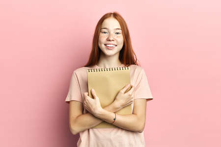Portrait of intelligent cute clever happy female student wearing casual t-shirt holding exercise book in hands isolated on pink background copy-space, lifestyle, free time