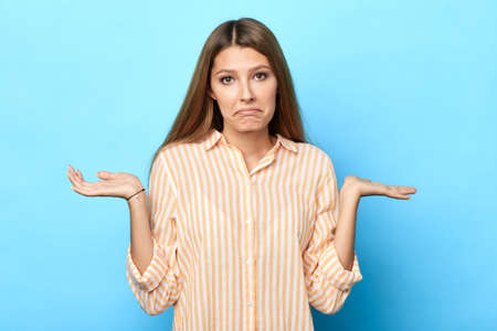 doubtful shocked girl shrugging shoulders, she doesnt know how to solve a problem, what present to give on holiday , close up portrait. isolated blue background. confusion concept. I dont know Imagens