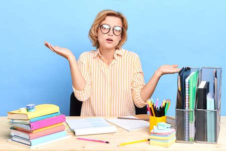 worried woman cannot solve the problem, close up portraitm secretary shrugging her shoulder, isolated blue background, studio shot