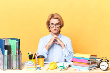 Serious business confident woman keeping her hands together sitting at her work desk, isolated on yellow background, close up portrait, studio shot, profession, occupation