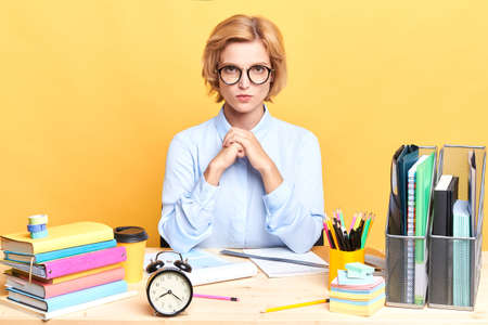 unhappy sad strict boss waiting her colleagues who was late, close up portrait, serious conversation. isolated yellow background Stock Photo