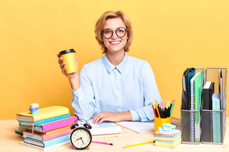Business woman holding a cup of coffee loking at the camera with positive expression, close up portrait, isolated yellow background, studio shot, lifestyle, free time 免版税图像
