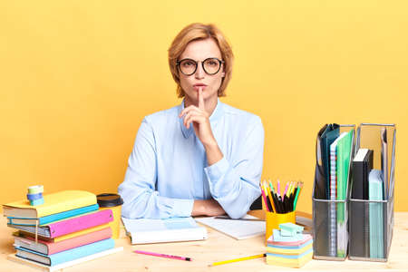 serious businesswoman with a finger on her lips, showing silence gesture, teacher asking students to calm down, stop talking. close up portrait, isolated yellow backgroun, body language. Stock Photo