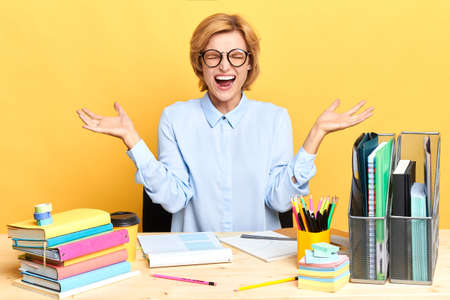 crazy funny woman screaming nervously while sitting at the table, secretary hates her work and boss, negative feeling and emotion, student cannot prepare for exams Stok Fotoğraf - 130652902