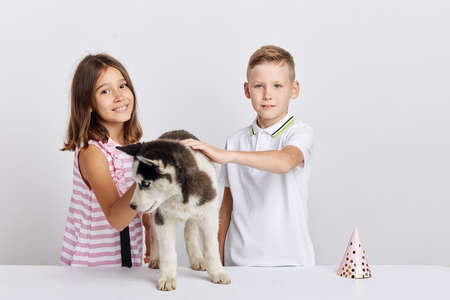 beautiful girl and good looking boy have received a present on their birthday, close up photo. isolated white background, studio shot, free time, spare time Stockfoto