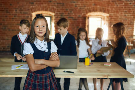 tanned beautiful girl in blouse, vest and checked skirt standing with crossed arms her partners doing their work at workplace. close up photo
