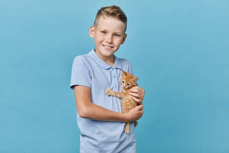 little boy in light blue T-shirt takes care of kitten. close up photo. happy childhood. close up portrait