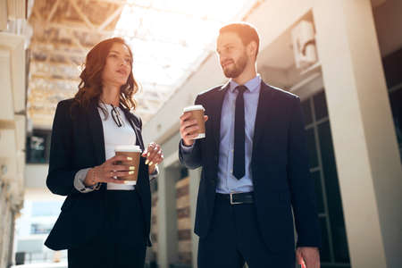 good looking young ambitious woman expressing her point of view on the problem while handsome bearded man is standing and listening to her very attentively