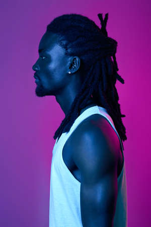 profile of handsome Afro guy with stylish dreads, close up side view portrait, stylish and fashion concept. isolated pink and violet background Standard-Bild