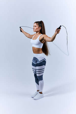 fit girl training with rope at sport club, full length side view photo. girl leads healthy lifestyle.free time, spare time, pastime