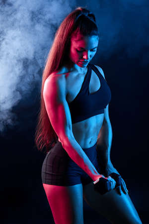 awesome young woman with long black hair developing her muscles, close up side view photo. isolated black background, stssudio shot.