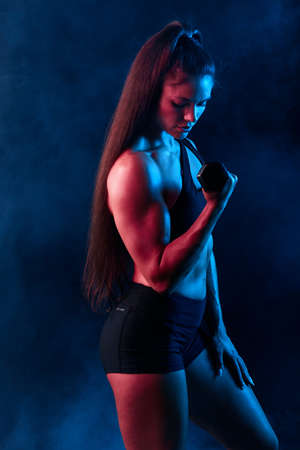 attractive ambitious fitness woman working out with dumbbell, close up side eview photo. isolated black background, studio shot, health and body care