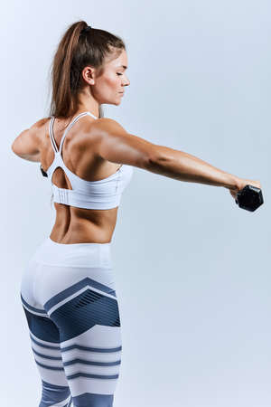 motivated woman with closed eyes comcentrated on workout process, willpower, leisure, hobby, interest. back view photo. copy space