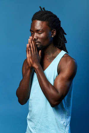 calm relaxed man with closed eyes praying with hands together asking for forgiveness smiling confident.close up side view portrait, isolated blue background, studio shot.