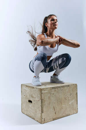 muscular sweaty girl doing squats on the box, keeping fit, full length photo. isolated white background, studio shot Banco de Imagens