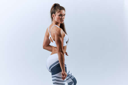 muscular pleasant tanned woman having a break after cross fit training. close up back view photo, isolated white background, studio shot