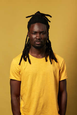 attractive african street guy in yellow T-shirt looking at the camera, close up photo.clothes concept