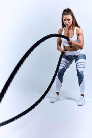 motivated strong girl training with rope . full length photo. motivation, wellness, wellbeing . isolated white background, studio shot
