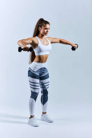active good looking woman raising dumbbells, trying to keep balance. full length side view photo. isolated white background. Banco de Imagens