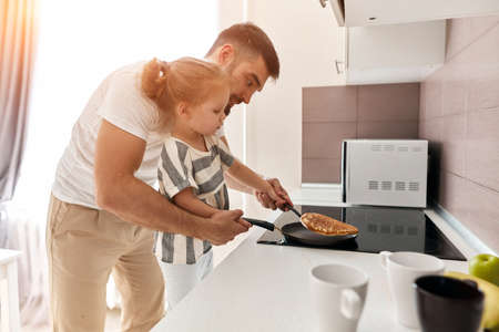 young father and his beautiful blonde daughter enjoying cooking pancakes for mother in the kitchen at home Stockfoto