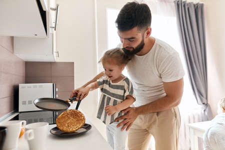 bearded father helping child to turn over the pancake in the kitchen, close up photo. Stockfoto