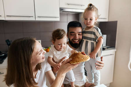 cheerful happy family gets pleasure from eating pancake, close up photo, leisure, pastime