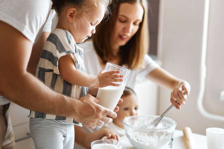 parents and kid preparing cookies in the kitchen, close up side view photo.