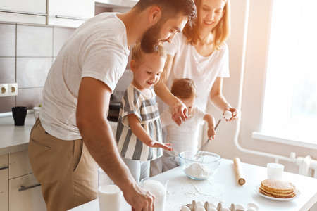 young cheerful couple and their kids trying to cook cake. close up side view photo
