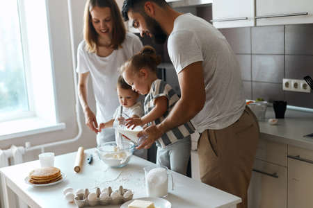 little girl helping her father and mother with cooking, adding milk to the paste, close up side view photo Stockfoto