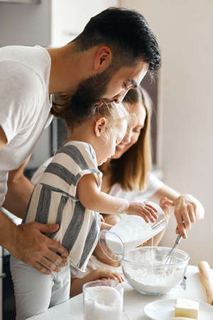 little girl pouring milk to pastry. close up side view photo. Stockfoto