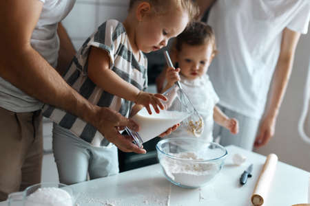 little kids making cream for cake, parents helping them in the kitchen. close up side view photo
