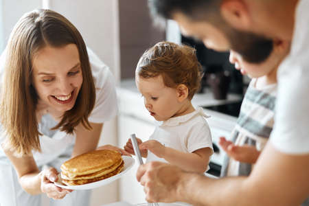 cheerful beautiful woman giving pancakes to her nice kid. close up side view photo. help yourself.