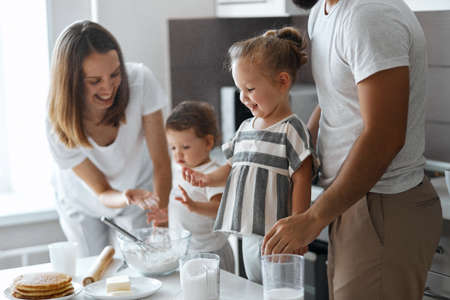 blkonde cheerful little girl touching flour with fingers. close up sside view photo
